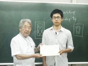 学校長と昨年度のスカラーシップ特待生として表彰を受けた古賀啓二さん