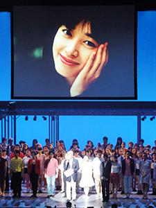 故夏目雅子さんの遺影の下で挨拶する「夏目雅子ひまわり基金」の小達代表事務局長