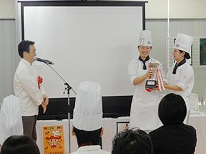 横田審査委員長から優勝杯を受ける札幌チーム