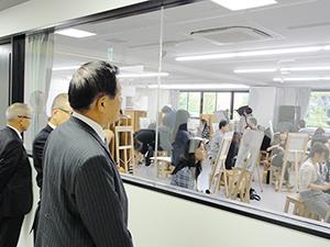 デッサンを描く学生たちの授業を見る佐藤会頭