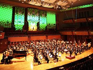 滋慶学園グループの運営開始を記念して開かれた「ザ・シンフォニー2014キックオフコンサート」で演奏する専属オルガニスト、片桐聖子さんと滋慶COMビッグバンド。片桐さんの座るパイプオルガンを中心にプロジェクションマッピングの映像が出現し、生まれ変わったホールの新シーンを演出した