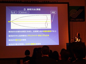 「優秀プラン発表会」で低出力半導体レーザー鍼灸針システムの開発に関するビジネスプランをプレゼンする西岡さん