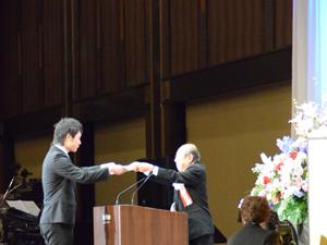 「ラブラブスイーツ」の店舗運営取り組みで大きな成果をあげて理事長賞を受賞。チームを代表して表彰状を受け取るNCA製菓・製パン科の栁澤拓希さん。