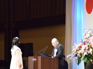 近藤雅彦JESC室長から表彰されるNCA総合デザイン科の村田恭奈さん。アメリカのアニメ映画「プロモーションツール制作」が高い評価を受けました。