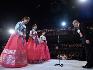 色艶やかな韓服で賞状を受けとるリ・ボラさん(左)、ガン・ウンジさん(中)、ユン・ジヨンさん(右)。